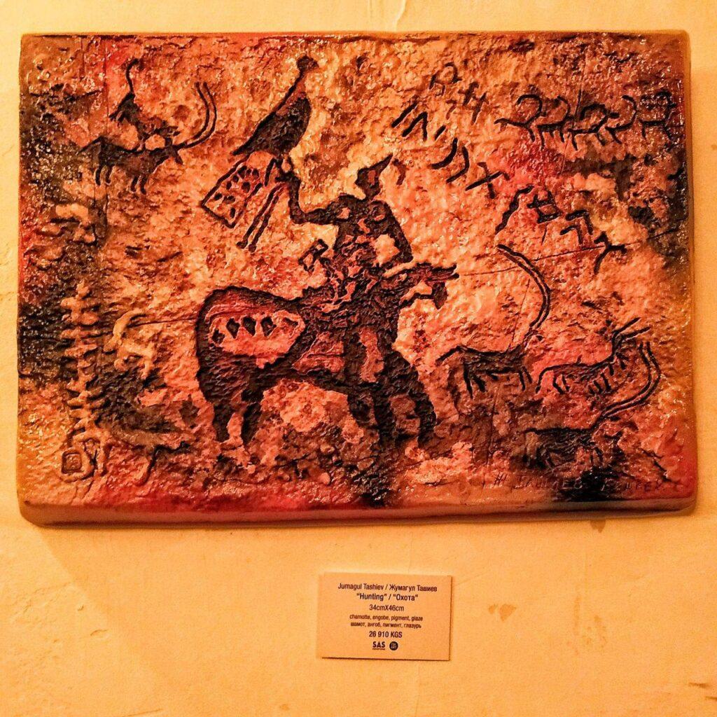 Фотография резьбы из дерева в стиле наскальных рисунков с изображением охотника на коне и с охотничьим соколом на руке